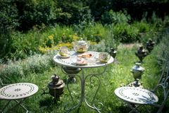 Tea ceremony at the green garden in the courtyard of the house. Kettle with coffee or tea with two cups and few sweets on the table. Still life. Samovars on Stock Images