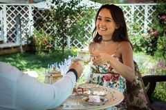 Tea ceremony at the green garden in the courtyard of the house. Young happy women sits together with boyfriend at the table with drinks and sweets. Couple Royalty Free Stock Image