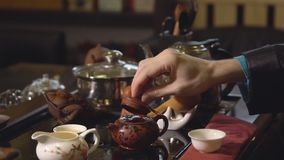 Tea ceremony. Tea maker pours boiling water into the teapot.  stock video footage