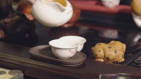 Tea ceremony. Master pours tea on white cups.  stock video footage