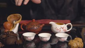 Tea ceremony. Master pours tea on white cups.  stock footage