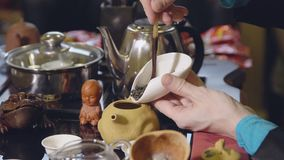 Tea ceremony. The master spoons the green tea leaves into the kettle with a wooden spoon.  stock video