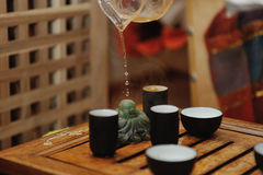 Tea ceremony. Moments of tea ceremony close up. Figurine of jade Buddha  changes color when hot drink gets on it Royalty Free Stock Photos