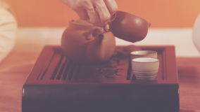 Tea ceremony. Orange toning. Tea ceremony. A man pours green tea from bowl into the cups. Ceramic utensils stand on a special tea table. Brewing tea in chinese stock video footage