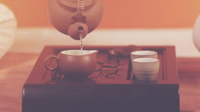 Tea ceremony. Orange toning. Tea ceremony. A man pours green tea from a kettle into the bowl. Ceramic utensils stand on a special tea table. Brewing tea in stock video