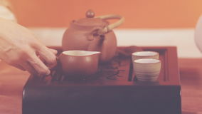 Tea ceremony. Orange toning. Tea ceremony. A man pours green tea from a kettle into the bowl and cups. Ceramic utensils stand on a special tea table. Brewing tea stock footage