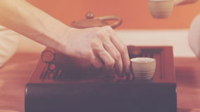 Tea ceremony. Orange toning. Tea ceremony. A man and woman sitting in lotus position take cups with green tea. Ceramic utensils stand on a special table. Brewing stock footage