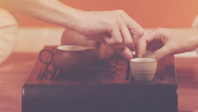 Tea ceremony. Orange toning. Tea ceremony. A man and woman take cups with green tea. Ceramic utensils stand on a special table. Brewing tea in chinese traditions stock video