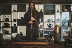Tea master playing flute before tea ceremony. Tea ceremony is perfomed by tea master royalty free stock images