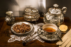 Tea ceremony with silverware and chinaware. Cookies and lemon Royalty Free Stock Image