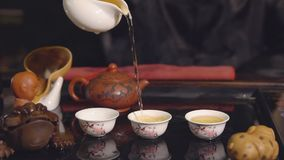 Tea ceremony. Master pours tea on white cups. Tea ceremony. Slow motion of master pours tea on white cups stock video footage