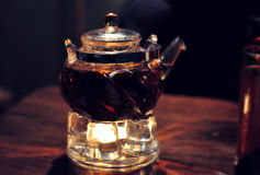 Tea ceremony, tea leaves in boiling water in a glass pot on a wooden table Royalty Free Stock Photography