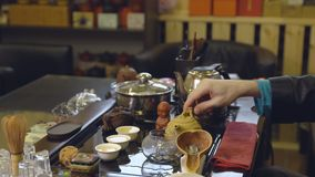 Tea ceremony. Tea maker pours boiling water into the teapot.  stock footage