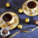 Tea ceremony, tea party. Two tea cups of gold color with black t. Ea, candy, chocolate on a lilac color background Stock Image