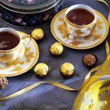 Tea ceremony, tea party. Two tea cups of gold color with black t. Ea, candy, chocolate, cloth and box with cookies on a lilac-colored background Royalty Free Stock Images