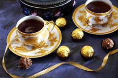 Tea ceremony, tea party. Two tea cups of gold color with black t. Ea, candy, chocolate and box with cookies on a violet background Stock Photo