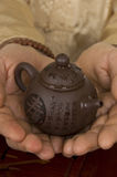 Tea ceremony. Teapot in hands of tea ceremony master close up Stock Images