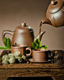Tea ceremony. Vertical photo, of the clay teapot tea flow in  cup on brown background,  tea ceremony Royalty Free Stock Photography