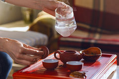 The tea ceremony. The woman pours hot water into the teapot Stock Photography