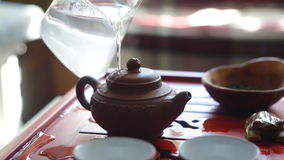 The tea ceremony. Woman scald the teapot before brewing tea. stock footage