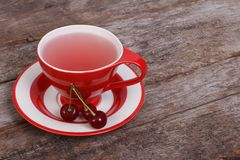 Tea with cherry berries on old wooden board Royalty Free Stock Images