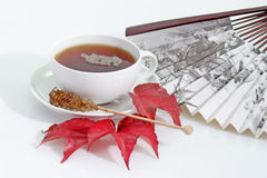 Tea from china. A cup of tea with fan and autumn leafs on bright background Royalty Free Stock Image