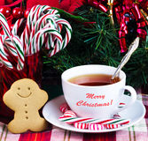 Tea with Christmas candy. And gingerbread man on holiday's background Stock Photo