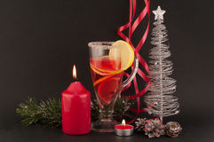 Tea and Christmas tree. Tea, christmas tree, candles, lights, cones, lemons, red ribbons on black background royalty free stock photography