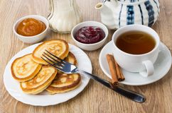 Tea with cinnamon, pancakes, bowls with jam, teapot and sugar Stock Images