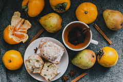 Tea, cinnamon sticks, muffins, pears, star anise and persimmons Royalty Free Stock Photo
