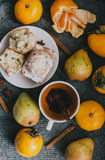Tea, cinnamon sticks, muffins, pears, star anise and persimmons Royalty Free Stock Images
