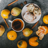 Tea, cinnamon sticks, muffins, pears, star anise and persimmons. Tea, cinnamon sticks, muffins, pears, star anise, mandarin and persimmons in instagram style Royalty Free Stock Image