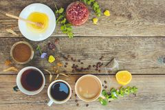 Tea, coffee, cocoa in cups, chicory, lemon, mint, jam made of rose petals, dried lime, honey. On the old wooden background. Toned image. Top view Royalty Free Stock Images