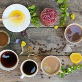 Tea, coffee, cocoa in cups, chicory, lemon, mint, jam made of rose petals, dried lime, honey Royalty Free Stock Image