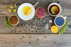 Tea, coffee in cups, chicory, lemon, mint, jam made of rose petals, dried lime, honey. On the old wooden background. Toned image. Top view Royalty Free Stock Photo