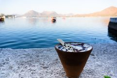 Tea and coffee in earthenware pots on a lakeside. Serene shot of tea and coffee in earthenware cups with chocolate syrup set on the banks of a beautiful blue Royalty Free Stock Image