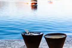 Tea and coffee in earthenware pots on a lakeside. Serene shot of tea and coffee in earthenware cups with chocolate syrup set on the banks of a beautiful blue Royalty Free Stock Photos