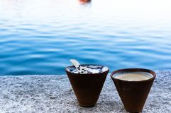 Tea and coffee in earthenware pots on a lakeside. Serene shot of tea and coffee in earthenware cups with chocolate syrup set on the banks of a beautiful blue Royalty Free Stock Images