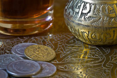 Tea and coins over an tray. Tea and coins over an arabic tray royalty free stock images