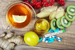 Tea for cold and flu. Vitamin tea, honey, ginger, lemons and viburnum. Thermometer and tablets. Medicines for colds Royalty Free Stock Photo