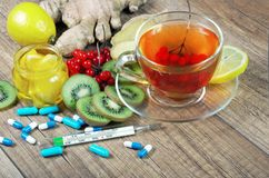 Tea for cold and flu. Vitamin tea, honey, ginger, lemons and viburnum. Thermometer and tablets. Medicines for colds Royalty Free Stock Photos