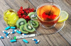 Tea for cold and flu. Vitamin tea, honey, ginger, lemons and viburnum. Thermometer and tablets. Medicines for colds Stock Photo