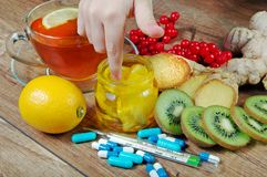 Tea for cold and flu. Vitamin tea, honey, ginger, lemons and viburnum. Thermometer and tablets. Medicines for colds Stock Images