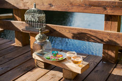 Tea with color figure biscuits on the outdoor. Beautiful wooden veranda overlooking the lake. Tea with color figure biscuits Stock Image