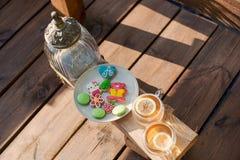 Tea with color figure biscuits on the outdoor veranda  overlooking lake shore. Beautiful wooden veranda overlooking the lake. Tea with color figure biscuits Stock Photos