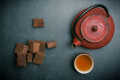 Tea composition with marshmallow, tea cup and iron teapot on dark background. royalty free stock photo