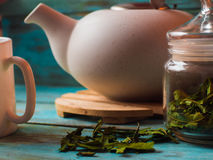 Tea concept, cup with teapot decorated with green leaf tea royalty free stock photos