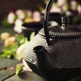 Tea concept, cups with tea and traditional teapot decorated with Stock Photos