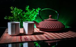 Tea concept. Japanese tea ceremony culture east beverage. Teapot and cups on table with bamboo leaves on sunset. Tea concept. Japanese tea ceremony culture east royalty free stock photo
