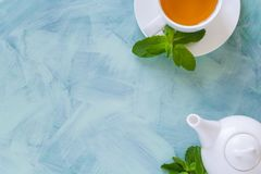 Tea concept. Teapot and cup with green herbal tea decorated mint leaves. On wooden background. Top view. Copy space. Flat lay Royalty Free Stock Photography